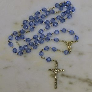 "Elegant centerpiece depicting Our Blessed Mother - Vibrant, sapphire-blue glass beads - Highly detailed pewter Crucifix - Includes ""How to Pray the Rosary"" folder - Blessed by the Vincentian Priests of Our Lady of Angels - Comes with a blue velveteen pouch"